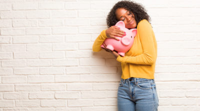 Young black woman happy extra cash hugging piggy bank
