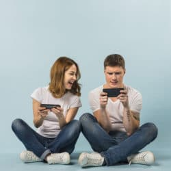 Young-couple-enjoying-the-video-game-on-cellphone-against-blue-backdrop -- how to make money playing video games, teen jobs, ways to make money