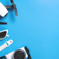 Hi tech travel gadget and accessories on blue copy space - 10 Ways to Make Extra Money With Drones - Starting A Drone Business