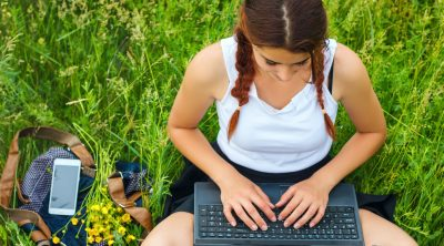 student sitting with a laptop on the grass, top view