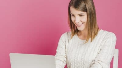 smiling-young-woman-working-laptop-front-pink-wall