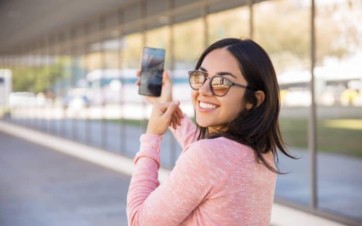 Happy pretty young lady taking selfie photo outdoors