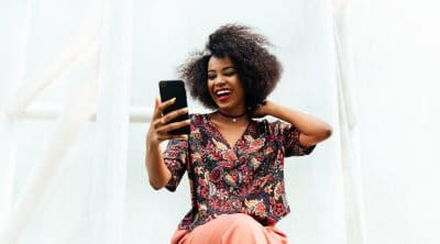 Laughing afro-american girl watching a funny movie on smartphone outdoors.