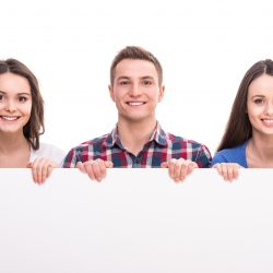 Group of smiling students are sitting over white background.