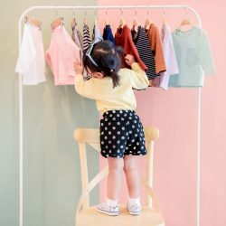 soft-focus-two-years-old-child-choosing-her-own-dresses-from-kids-cloth-rack